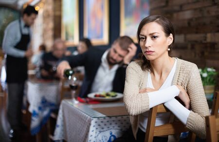 Portrait of upset evil dumpish man and woman in the restaurant on meeting