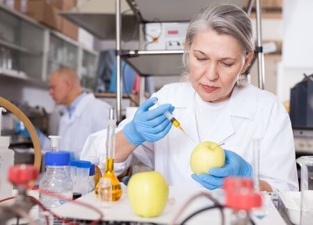 Mature female scientist injecting reagent from syringe into apple, performing scientific researching of food genetic modification in laboratory
