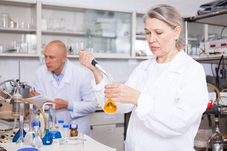 Professional female chemist working in laboratory, mixing chemical agents during experiment