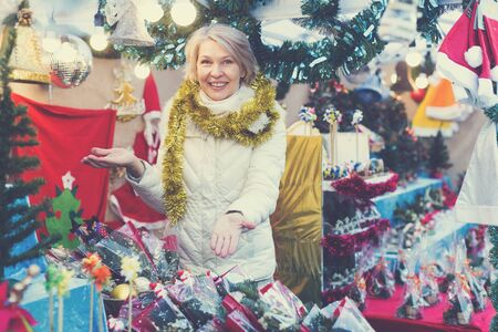 Adult woman is choosing Christmas bouqet in the market outdoor.