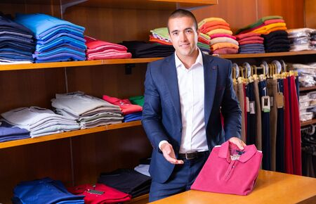 Male seller lays out shirts on shelves in a clothing store Stockfoto