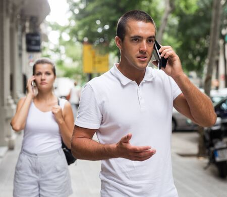Young man and woman talking on smartphones on street Foto de archivo - 133745412