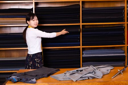 Young Chinese salesgirl working in fabric store, demonstrating wide range of stylish cloth Stockfoto