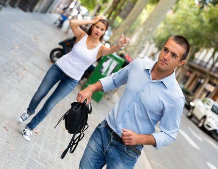 Male thief stealing woman bag on street of city Foto de archivo - 133745418