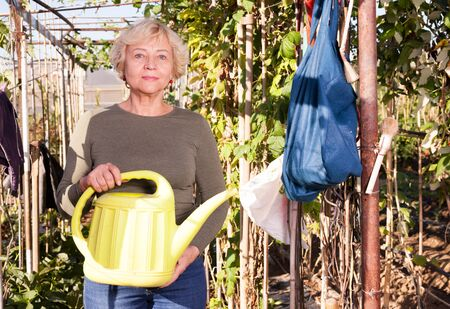 Positive mature woman holding watering can in her hands in plantation