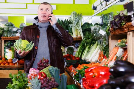 Serious man talking on mobile phone while doing shopping in vegetables shop