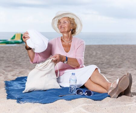 Positive mature woman resting on sand after beach walk Stockfoto