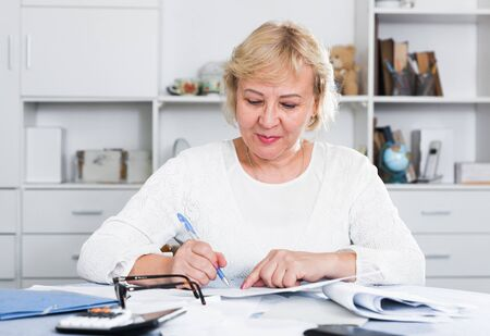 Mature woman with documents in her hands makes up her personal budget