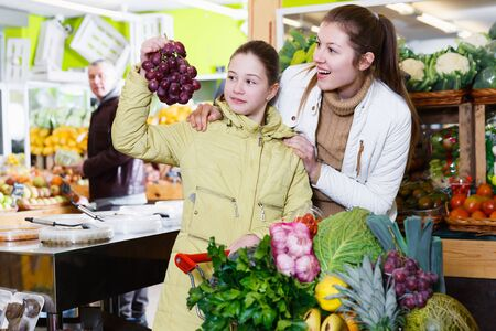 Portrait of positive mother with daughter shopping together in fruit market Stock Photo
