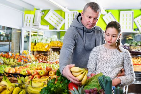Friendly father and daughter shopping together in the greengrocery, choosing ripe bananas
