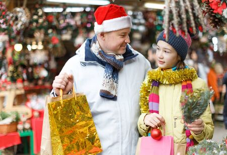Cheerful preteen girl with father shopping decorations on Christmas market