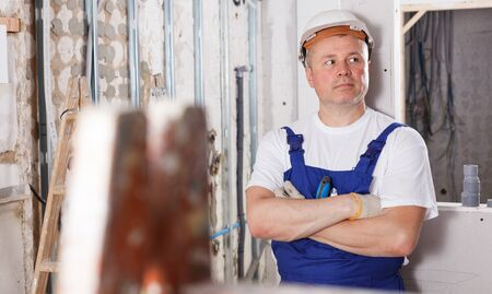 Portrait of experienced construction worker standing at indoors building site