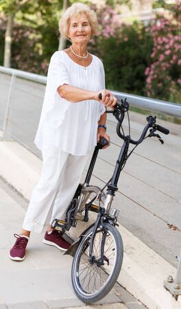 Portrait of retired woman resting near bike after ride in park