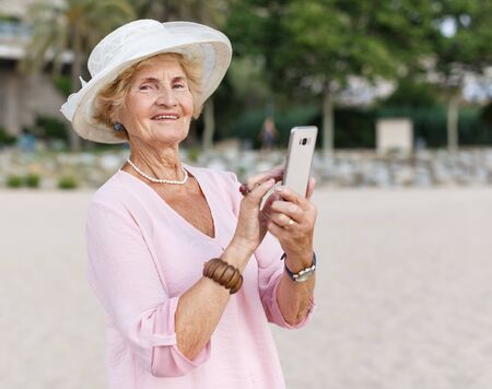 Mature woman browsing on smartphone while relaxing at seashore Stock fotó