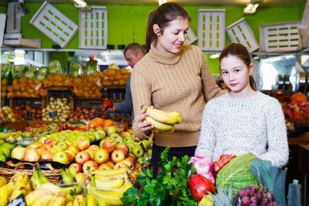 Happy preteen girl with attractive young mother choosing fresh ripe fruits in store Stock Photo