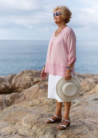 Portrait of elderly woman standing relaxed at seashore and smiling