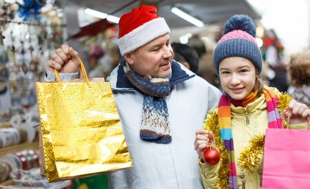 Preteen girl with her father looking happy with shopping bags on outdoor Christmas fair