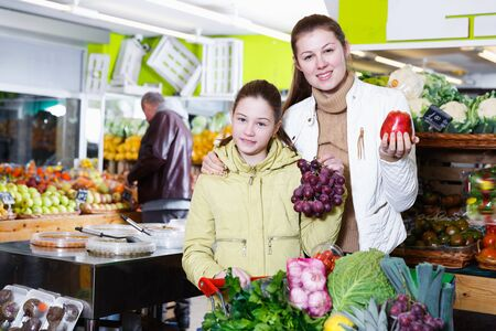 Portrait of cheerful young mother with daughter shopping together in fruit market Stock Photo