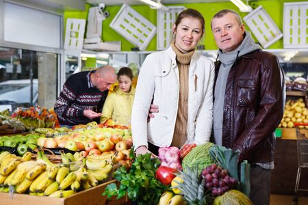 Portrait of loving couple with full shopping cart at fruit market