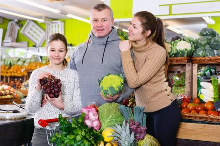 Portrait of friendly family of three with a shopping cart full of fruits and vegetables in greengrocery Stock Photo