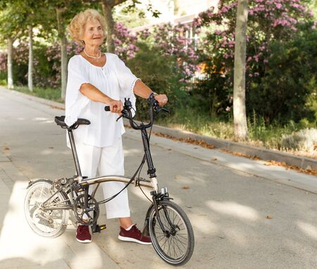 Active elderly woman walking with bike on park path Фото со стока - 133745510