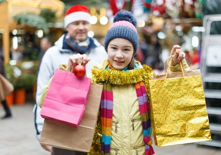 Portrait of smiling teen girl with father holding shopping bags with purchases on street Christmas market