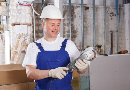 Confident male contractor using professional angle grinder in overhauls indoors Reklamní fotografie