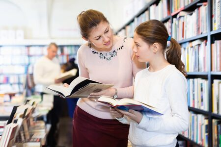 Friendly family of  cheerful mother and daughter browsing books together in bookstore