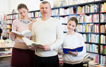 Portrait of happy intelligent family with teenager browsing books in library
