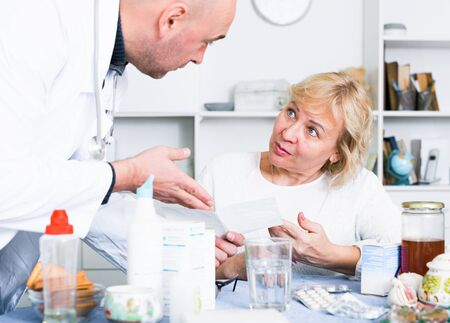 Portrait of a mature woman and a doctor at a table with medicines 写真素材