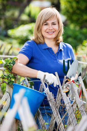 Smiling pleasant blond mature woman  holding horticultural tools in garden on sunny day