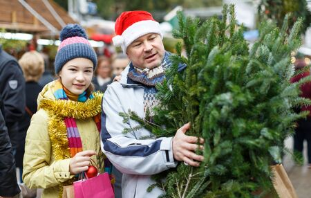 Portrait of smiling teen girl and her loving father with fresh green fir tree on Christmas street market Zdjęcie Seryjne