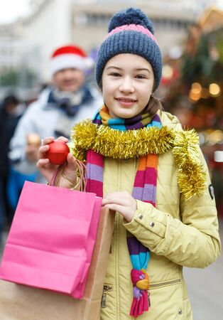 Smiling cute preteen girl holding bags after shopping with father on outdoor Christmas market Zdjęcie Seryjne