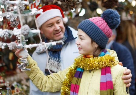 Cheerful teenage girl looking for decorations on Christmas street market while shopping with her father