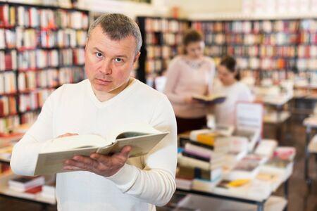 Positive male reading interesting books in bookstore 版權商用圖片