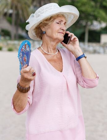 Positive mature woman talking on mobile phone and relaxing at seashore Stockfoto