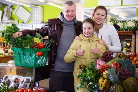 Happy young family with small daughter giving thumbs up in fruit shop