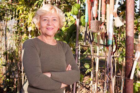 Portrait of cheerful senior woman in garden on sunny day Stock Photo