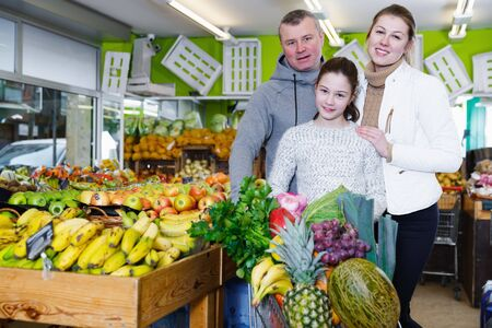 Happy family with smalldaughter standing with full grocery cart after shopping in fruit store