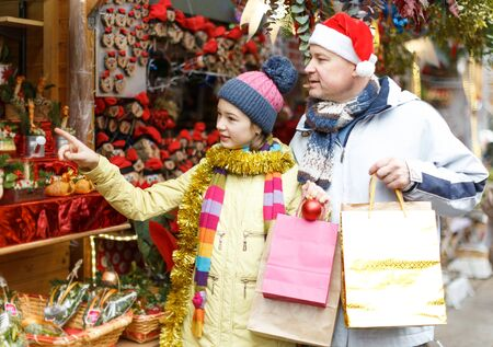 Young father with daughter having fun on Christmas fair, selecting decoration for home Zdjęcie Seryjne