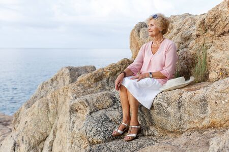 Happy senior woman sitting at seaside and admiring nature