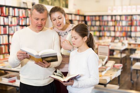Adult family with preteen daughter reading interesting books in bookshop Zdjęcie Seryjne