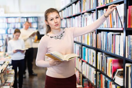 Young  cheerful positive  smiling  attractive female looking for necessary books on shelves in bookstore