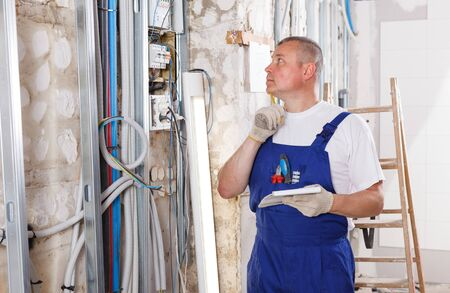 Confident builder handyman examining room and planning construction works
