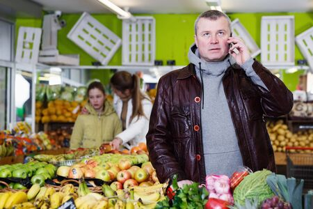 Man customer speaking by phone in vegetable and fruit store during purchasing Stock Photo