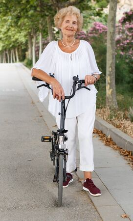 Senior caucasian woman having break in cycling, resting near bike