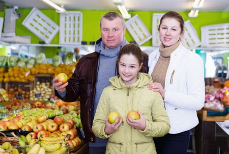 Family with small daughter choosing sweet ripe apples in in fruit market