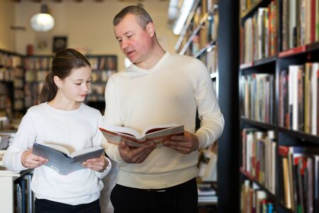 portrait of serious adult man with daughter looking for interesting books in library Zdjęcie Seryjne