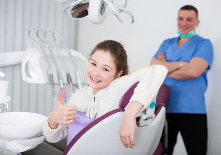 Teenage girl smiling and showing thumb up in modern dental clinic