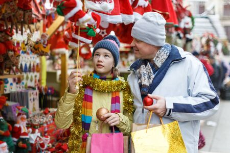 Happy teen girl with her loving father choosing Xmas decoration on outdoor market